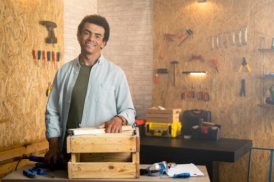 Portrait of a smiling carpenter in workshop