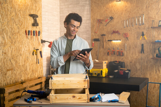 Carpenter in workshop holding and looking at tablet