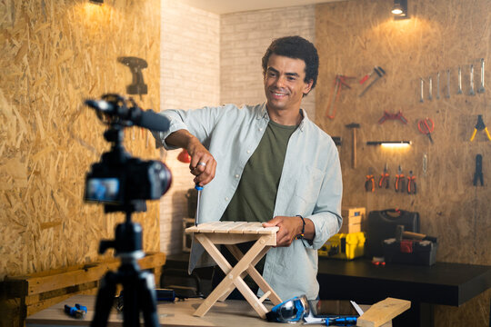 DIY carpenter filming a blog showing how to tighten up a wooden chair