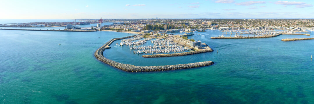 Panoramic shot of Fremantle's Challenger Harbour on a sunny day with boats, yachts. trees and groyne