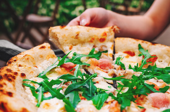 woman Hand takes a slice of meat neapolitan Pizza with Mozzarella cheese, ham, bacon, Spices and chicken in cafe outdoor