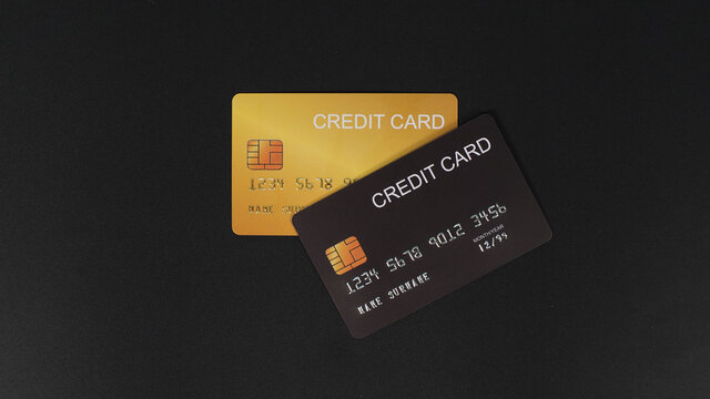 Black and gold credit card isolated on black background.
