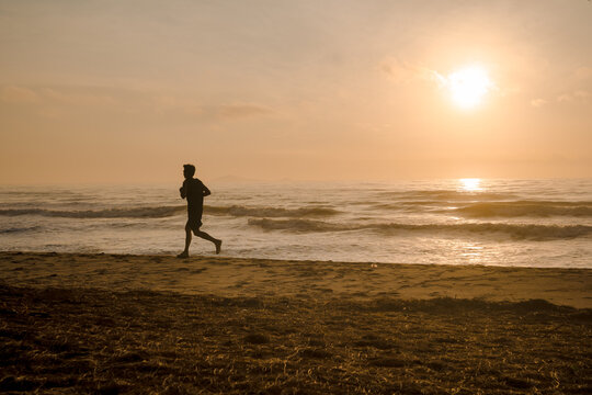 silhouette man run on beach with sunrise and sea background