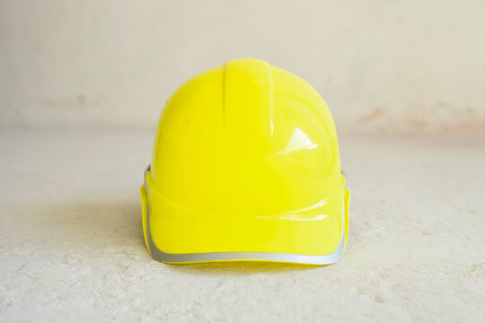 Yellow hardhat. Construction worker safety helmet on cement floor, front view