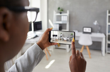 Fototapeta Black designer taking office interior photos, making presentation or video calling client using smart phone app. Rental agent or realtor shows work space while giving tour around display apartment obraz