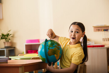 Fototapeta amazed asian girl pointing at globe and looking at camera in montessori school obraz