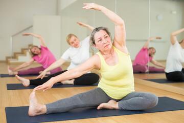 Fototapeta Mature European women are doing head-to-knee forward bend obraz