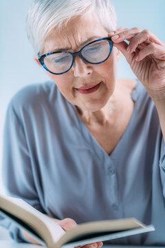 Glaucoma. Senior Woman a Reading Book, Having Ocular Tension.