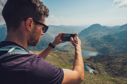 Traveling man taking picture of mountains on smartphone on sunny day