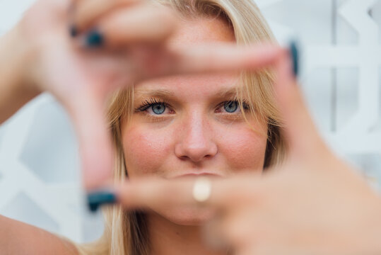 Charming woman showing framing gesture in city