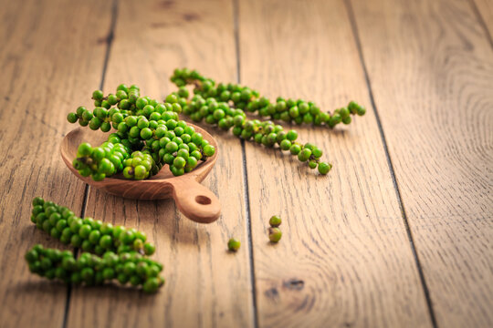 Fresh green peppercorns on wooden kitchen table