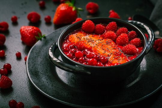 Breakfast red smoothie bowl with chia seeds, strawberry, raspberry and redcurrants