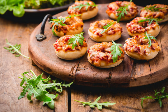 Small pizza in donut shape with rocket (arugula) and fresh salad