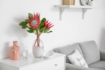 Fototapeta Chest of drawers with protea flowers in interior of room obraz