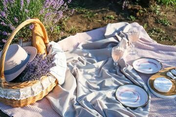 Fototapeta Wicker basket with drink and dinnerware for romantic picnic in lavender field obraz