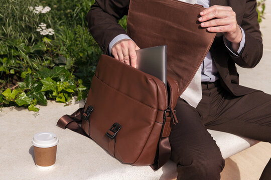 Anonymous mature businessman with laptop and briefcase on street