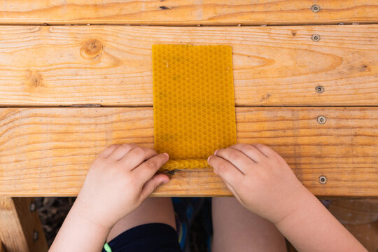 Crop kid creating beeswax candle at table