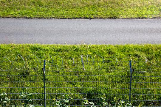 Hoher Zaun mit Stacheldraht als Absperrung