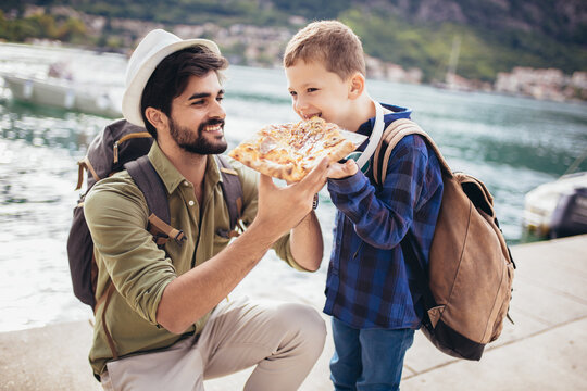 Father and son eating pizza. Happy, joyful family.