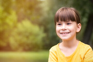 Happy little girl in a yellow t-shirt is looking away on a green background