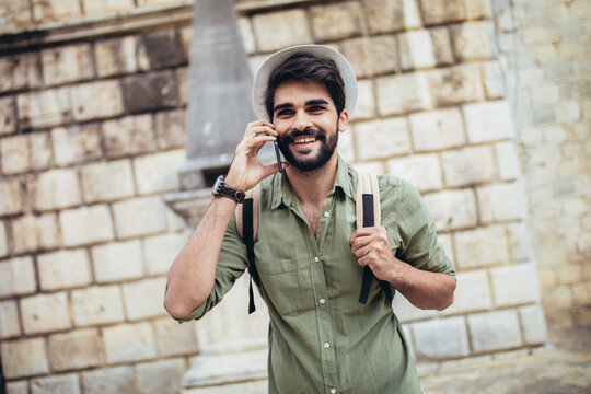 Handsome bearded tourist with backpack is making travel across city. Man using phone.
