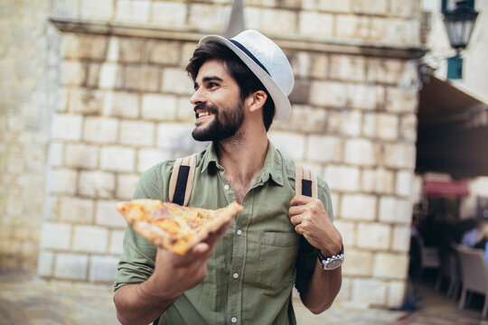 Young man eats a piece of appetizing pizza. Hungry guy holds a piece of pizza in his hands, looks at him and is going to eat it. Fast food.