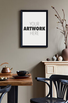 Creative composition of cozy and stylish dining room interior with mock up poster frame, wooden table, chair, black dishes and accessories. Sunny and light space. Neutral colors. Beige walls..