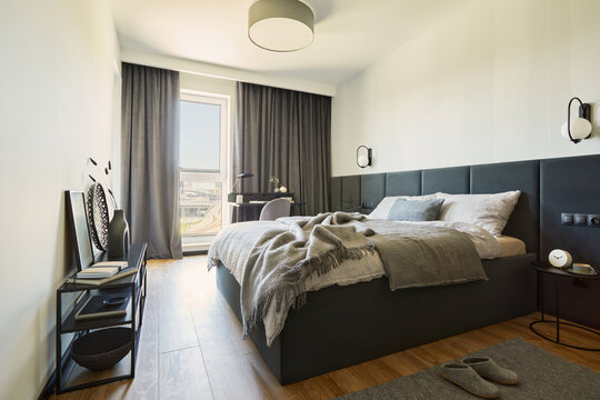 Stylish composition of small modern bedroom interior. Bed with linen bedclothe, black metal shelf and  elegant personal accessories. Neutral walls with black panels.  Minimalistic  concept. Template.