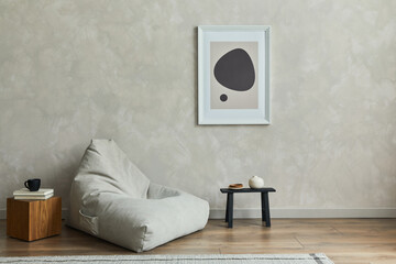 Fototapeta Stylish composition of minimalistic living room interior with mock up poster frame, grey pouf, black tiny coffee table, wooden cube and elegant personal accessories on it. Template. obraz