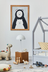 Obraz Stylish scandinavian child's room interior with mock up poster frame, creative bed, wooden cube, lamp, plush and wooden toys and hanging textile decorations. Grey walls, carpet on the floor. Template. - fototapety do salonu