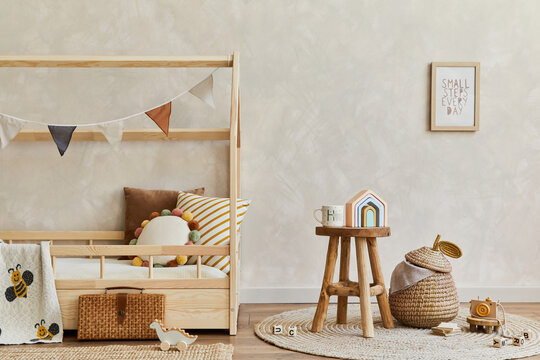 Stylish composition of cozy scandinavian child's room interior with wooden bed, coffee table, plush and wooden toys and hanging decorations. Creative wall, carpet on the floor. Copy space. Template.
