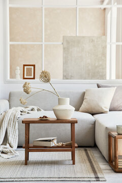 Creative composition of stylish and cozy living room with mock up poster frame, grey sofa, window, plaid, pillows and personal accessories. Beige neutral colors. Template.