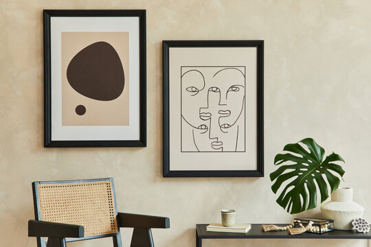 Creative composition of stylish modern living room interior with two mock up poster frames, black geometric commode, armchair, leaf in vase and personal accessories. Neutral corols. Template.