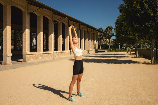 Caucasian female athlete in the sunlight stretching before sport