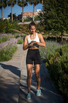 CaucasianSporty Caucasian woman looking at her smartwatch after running. Full body frontal photo
