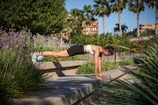 Athletic woman exercising push-ups in a park