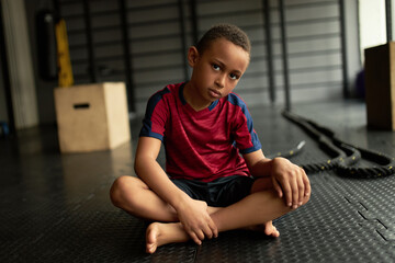 Serious latin boy tired after workout, feel lazy to exercise. Child chilling on floor in gym. No...