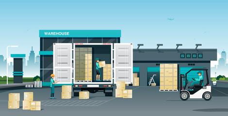Obraz Workers loading goods onto trucks in a warehouse. - fototapety do salonu