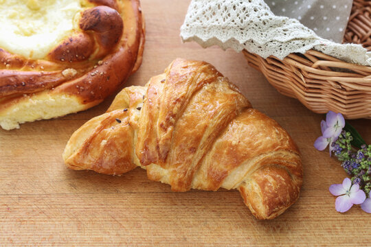 French croissant made of puff pastry on a wooden table.