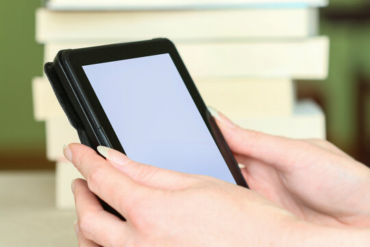 A woman is holding an e-book reader in her hands