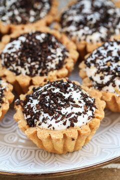 Tiny cupcakes with chocolate on the table.