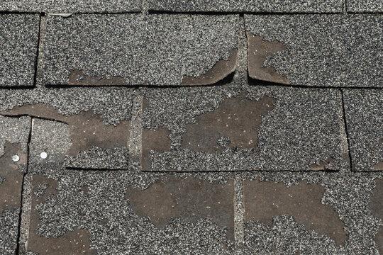 Broken worn asphalt roofing shingles fixit concept