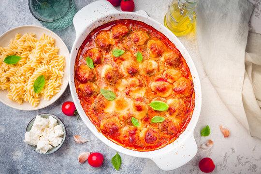 Homemade meatballs in tomato mozzarella sauce with basil and pasta in casserole