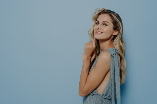 Curious sweet blonde girl with finger next to chin smiling at camera