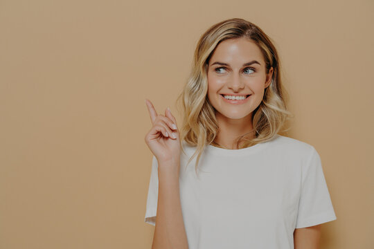 Positive young woman customer with blonde hair wearing white tshirt with pleasant smile pointing at copy space