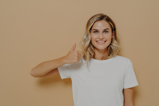 Happy young blonde female wearing white casual tshirt making thumbs up gesture and smiling cheerfully