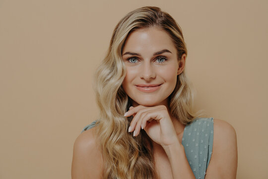 Calm and relaxed young blonde woman with hand under chin