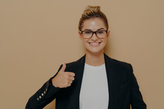 Portrait of positive woman office worker in spectacles and formal outfit showing thumb up and looking at camera