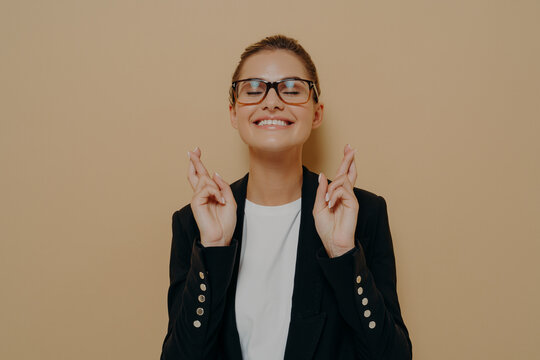 Young hopeful female student in eyeglasses crossing her fingers with hope and asking for good luck before exam
