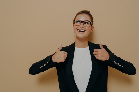 Positive female customer in eyeglasses with broad smile showing thumbs up with both hands